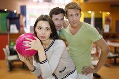 A mulher prepara-se ao throw da esfera; olhar dos homens Fotografia de Stock