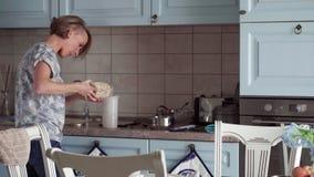 A mulher prepara um alimento e olha no smartphone filme