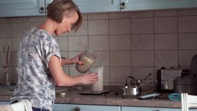 A mulher prepara um alimento e olha no smartphone video estoque