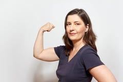Mulher presumido que dobra os músculos do bíceps fotografia de stock