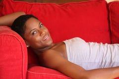 Mulher preta bonita no sofá vermelho Fotografia de Stock