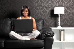 Mulher preta de sorriso feliz no Internet surfando do sofá Fotografia de Stock