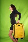 Mulher preta do vestido com mala de viagem amarela Foto de Stock
