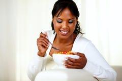 Mulher preta nova que come o pequeno almoço saudável Fotografia de Stock