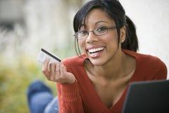 Mulher preta que usa o cartão e o portátil de crédito Fotografia de Stock Royalty Free