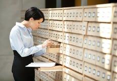 A mulher procura algo no catálogo de cartão Imagem de Stock Royalty Free