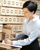 A mulher procura algo no catálogo de cartão Fotografia de Stock Royalty Free