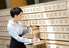 A mulher procurara algo no catálogo de cartão Imagens de Stock Royalty Free
