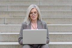 Mulher profissional atrativa que usa um portátil imagens de stock royalty free