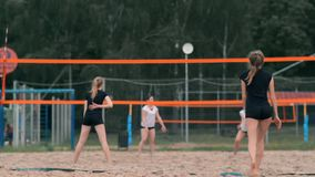 Mulher profissional do saque do voleibol no competiam da praia A rede do voleibol o jogador obstrui a vista ao aplicar-se filme