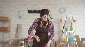 A mulher profissional do trabalhador novo nos monóculos usa skillfully as ferramentas da mão, mo lento filme