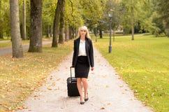 Mulher profissional elegante que puxa sua bagagem imagem de stock