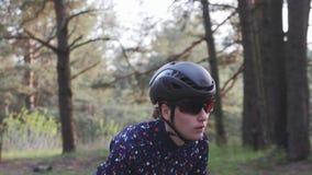 Mulher profissional focalizada desportivo do ciclista que monta uma bicicleta fora da sela Siga o tiro Conceito de ciclagem da es vídeos de arquivo