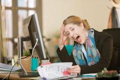 Mulher profissional forçada que grita em sua mesa fotos de stock royalty free