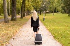 Mulher profissional loura que puxa uma mala de viagem imagens de stock royalty free