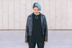 A mulher punk nova com azul tingiu o cabelo e um lookin do casaco de cabedal Foto de Stock
