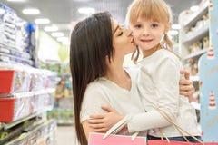 Mulher que abraça a menina e que beija no shopping fotografia de stock royalty free