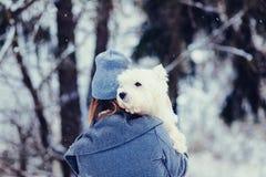 Mulher que abraça o cão branco do terrier fotografia de stock royalty free