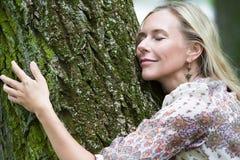 Mulher que abraça uma árvore imagem de stock royalty free