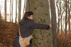 Mulher que abraça uma árvore Fotos de Stock Royalty Free