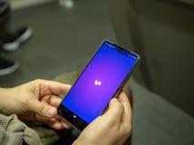Mulher que abre o app móvel de Lyft com logotipo na tela de Android ao comutar no metro imagem de stock royalty free