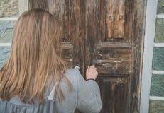 Mulher que abre a porta de madeira muito velha fotos de stock royalty free