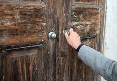 Mulher que abre a porta de madeira muito velha imagens de stock