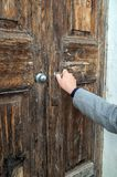 Mulher que abre a porta de madeira muito velha fotografia de stock