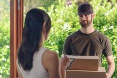 Mulher que aceita uma entrega de duas caixas de cartão Fotografia de Stock Royalty Free