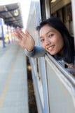 Mulher que acena um cumprimento de trem movente Fotografia de Stock Royalty Free