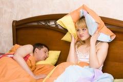 Mulher que acorda por seu marido que ressona Fotografia de Stock Royalty Free