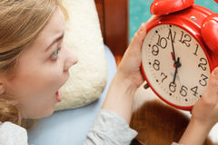 Mulher que acorda tarde desligando o despertador foto de stock