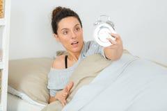 Mulher que acorda tarde na manhã que desliga o despertador imagens de stock royalty free