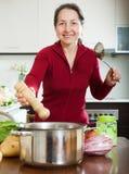 Mulher que adiciona o tempero na bandeja da sopa Imagem de Stock