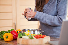 Mulher que adiciona a pimenta a seu guisado vegetal Imagens de Stock