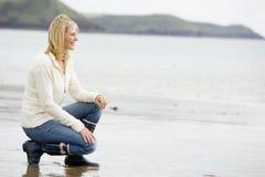 Mulher que agacha-se na praia Fotos de Stock Royalty Free