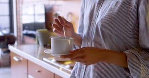 Mulher que agita o café na cozinha em casa 4k vídeos de arquivo