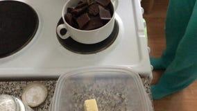 Mulher que agita o chocolate branco em uma placa O chocolate é derretido em um banho maria para fazer uma sobremesa E vídeos de arquivo