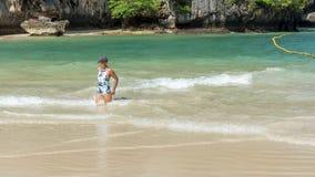 Mulher que ajoelha-se na água na ilha trropical fotografia de stock