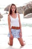 Mulher que ajoelha-se na areia da praia Imagens de Stock Royalty Free
