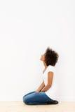 Mulher que ajoelha-se olhando uma parede branca Imagens de Stock Royalty Free