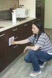 Mulher que ajoelha-se para limpar a mobília Imagens de Stock Royalty Free