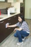 Mulher que ajoelha-se para limpar a mobília Fotos de Stock Royalty Free