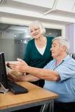 Mulher que ajuda ao amigo masculino em usar o computador na sala de aula Imagens de Stock Royalty Free