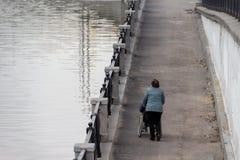 Mulher que ajuda a rolar uma cadeira de rodas com uma pessoa ao longo do passeio imagens de stock