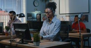 Mulher que ajuda a seu colega em um centro de apoio vídeos de arquivo