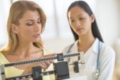 Mulher que ajusta a escala do peso ao estar pelo doutor fêmea Imagem de Stock