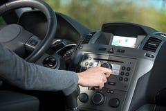 Mulher que ajusta um botão em seu carro Imagens de Stock