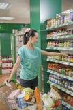 Mulher que alcança para o frasco na prateleira no supermercado, Pequim imagens de stock