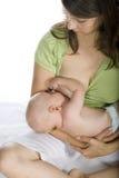 A mulher que alimenta um bebê Fotografia de Stock